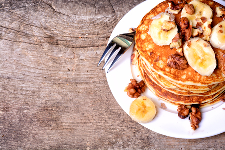 flapjacks: Pancakes with banana & walnut on wood background .