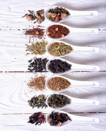 assortiment van droge thee in ceramische kommen op houten achtergrond.