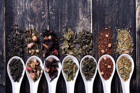 teas: assortment of dry tea in ceramic bowls on wooden background.