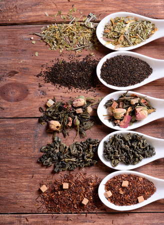 herbs boxes: assortment of dry tea in ceramic bowls on wooden background.