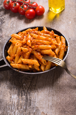 Penne Pasta  tagliatellei with tomato sauce on wooden table