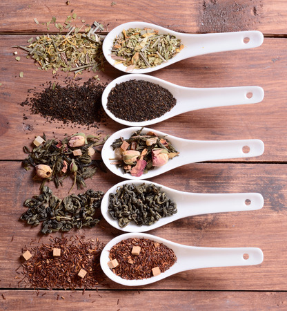loose leaf: assortment of dry tea in ceramic bowls on wooden background .