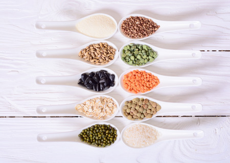 Cereals in ceramic bowls on wooden background.