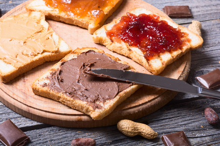nut nougat cream with chocolate , strawberry, apricot jam and peanut butter sandwich Stock Photo