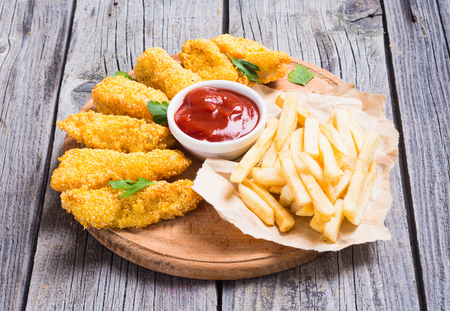 tenders: chicken strips and French fries  on rustic wooden background