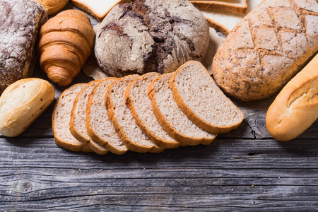 Fresh fragrant bread on wooden background . Food concept