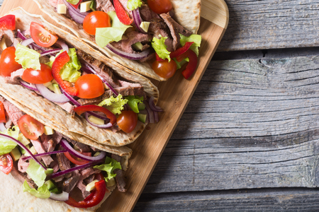 Mexican pork tacos with vegetables on wooden rustic background . Top view