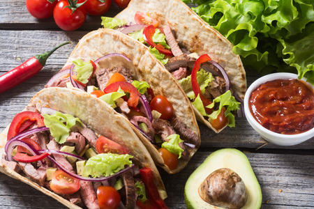 Mexican pork tacos with vegetables on wooden rustic background .