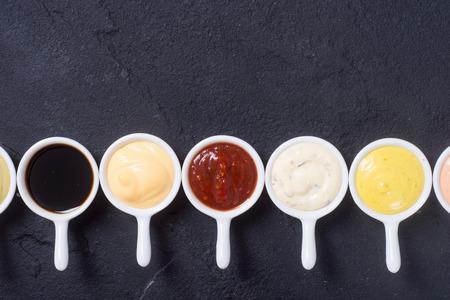 Set di salse in piattini bianchi. Vista dall'alto Archivio Fotografico - 83779564