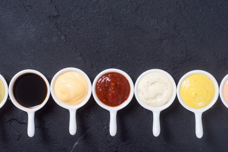 Set of sauces in white saucers . Top view