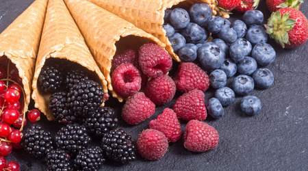 Berries in ice cream cone (raspberry , blueberry , strawberry , red currant , blackberry)