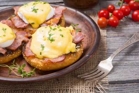 benedict: Eggs benedict with bacon on wooden background .
