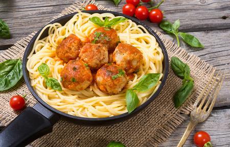 marinara sauce: Spaghetti in pan with meatballs and basil