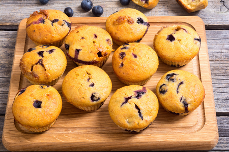 Banana muffins with blueberry on rustic background .