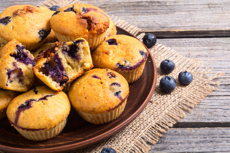 Banana muffins with blueberry on rustic background . copy space
