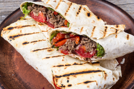 Homemade tasty burrito with vegetables and beef Standard-Bild