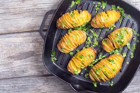 Frisch gebackene Hasselback Kartoffeln mit Petersilie. Standard-Bild - 87734462