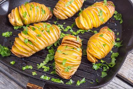 Frisch gebackene Hasselback Kartoffeln mit Petersilie. Standard-Bild - 87734465