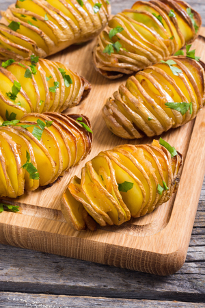 Freshly baked hasselback potatoes with parsley .