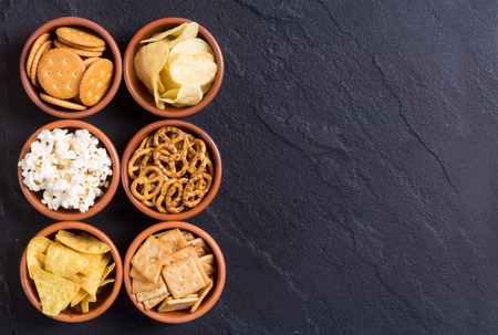 Frame . Mix of snacks : pretzels , crackers , chips , pop corn and nachos Archivio Fotografico
