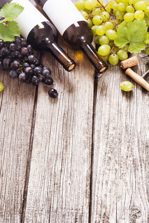 Red and white wine with grapes . On wooden background