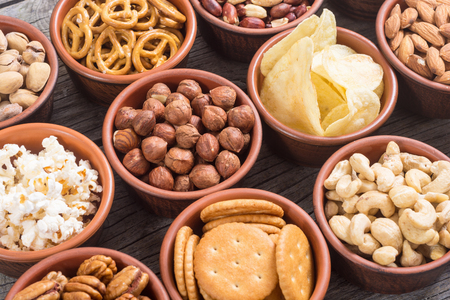 Mix of snacks : pretzels , crackers , chips , nuts and nachos Stock Photo