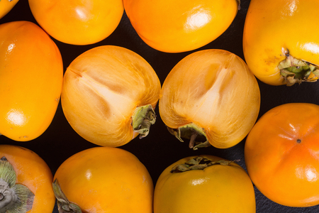 Delicious ripe persimmon fruit on stone background