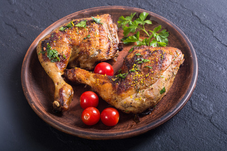 Grilled chicken legs with tomatoes and parsley