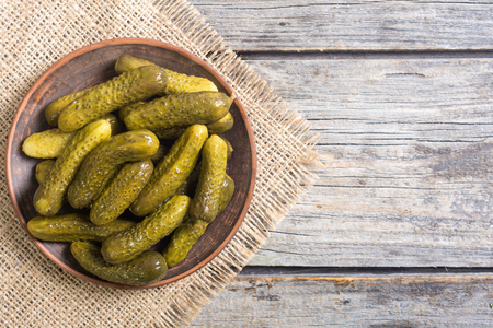 Pickles . Marinated cucumber in plate on wooden background . Imagens - 90916744