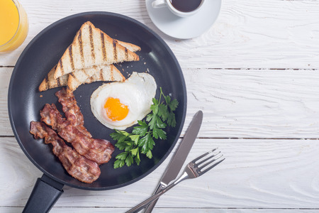 Breakfast with egg bacon and toasts . Food background