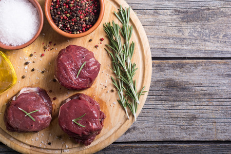 Raw fillet mignon with pepper , salt , rosemary and olive oil Stock Photo