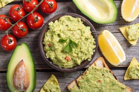 Guacamole met ingrediënten: avocado, citroen en tomaten. Mexicaans eten