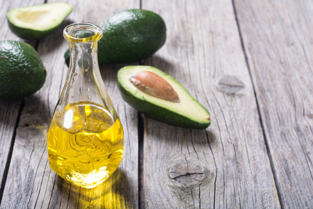 Fresh healthy green avocado and oil . With space for text