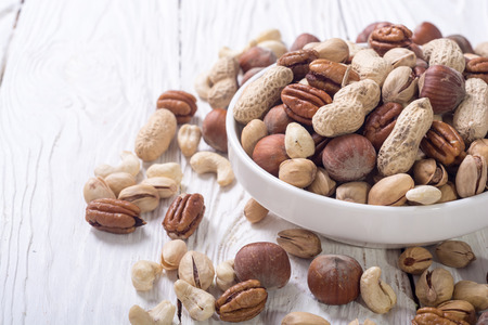 Mix of nuts in plate . pecan , hazelnut , pistachios , cashew and peanuts Stock Photo