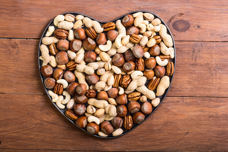 Mix of nuts in heart . Pecan , hazelnut , pistachios , cashew and peanuts . Love snacks