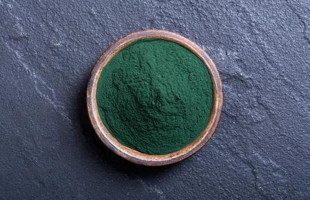 Green spirulina powder in bowl . nature medicine