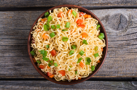 Instant noodles in bowl with carrot , tomatoes and onion Imagens