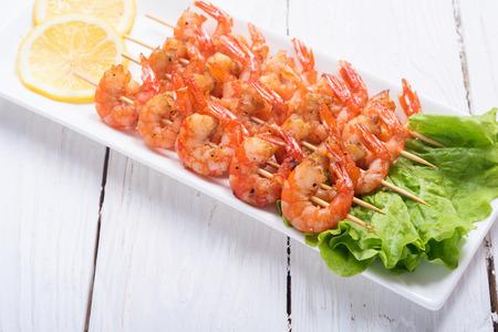 Fresh hot grilled shrimps skewers . Seafood backround .