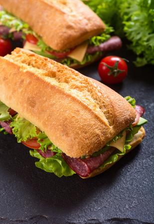 Ciabatta sandwich with lettuce , salami , cheese , avocado and tomatoes Foto de archivo