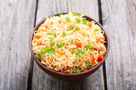 Instant noodles in bowl with carrot , tomatoes and onion Stock Photo
