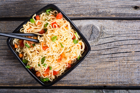 Instant noodles in bowl with carrot , tomatoes and onion 스톡 콘텐츠