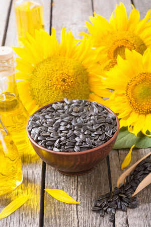 Ingredient  oil , seeds and sunflower on wooden background