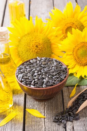 Olio, semi e girasole dell'ingrediente su fondo di legno Archivio Fotografico