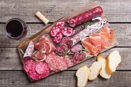 Assortment of sausages . Ham , salami and jamon on wooden board