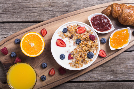 Breakfast with yogurt, granola, berries, orange juice, croissant and jam