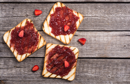 Toast with strawberry jam on rustic wooden background Banco de Imagens