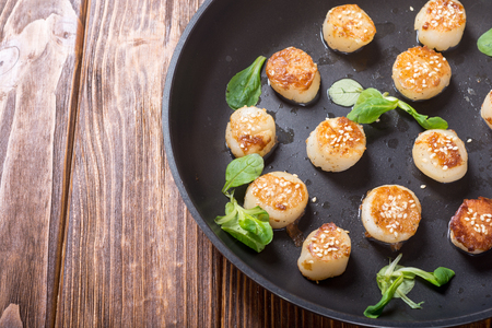 Fried scallops with lemon and salad . Seafood background