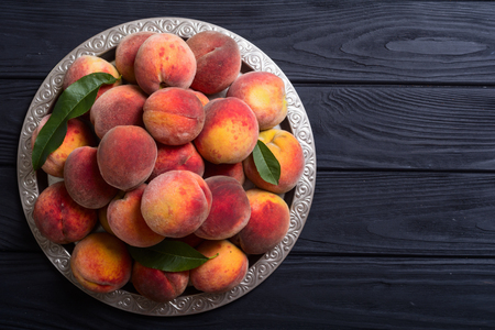 Ripe peaches fruit on rustic background . Summer healthy food Фото со стока