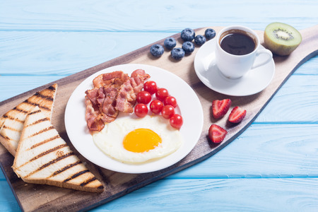 Breakfast with eggs, bacon, tomatoes, coffee and berries Stock Photo
