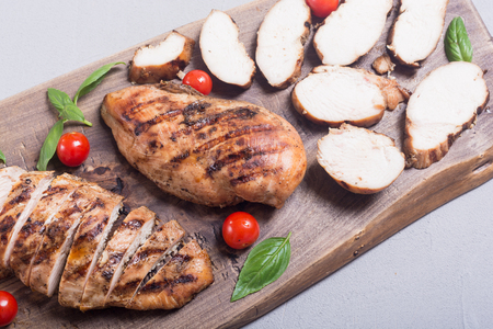 Grilled chicken breast ( fillet ) with basil and tomatoes . BBQ background 写真素材